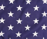 与白色星的美国国旗由后照的蓝色。 免版税库存图片
