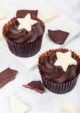 与白色星的黑暗的巧克力杯形蛋糕在大理石 免版税库存照片