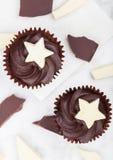 与白色星的黑暗的巧克力杯形蛋糕在大理石 免版税库存图片
