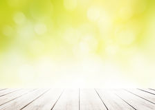 与白色木地板前景的迷离自然绿叶bokeh叶子墙纸在春天秋天公园背景 库存图片