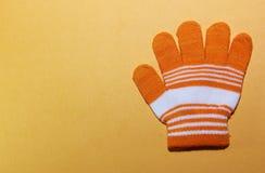 与白色条纹的一个儿童` s手套桔子说谎黄色表面,被展开的手指,能力上温暖您的在wint的手 免版税库存图片