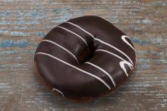 与白色条纹的巧克力多福饼在木背景 免版税图库摄影