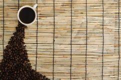 与白色杯子的咖啡豆在席子 库存照片