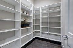 与白色架子和黑暗的地板的空的餐具室内部 库存照片