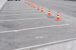 与白色标记和交通锥体的闭合的汽车停车场在街道上使用了在路的警报信号 库存图片