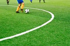 与白色标记线的绿色足球场草和男孩踢橄榄球 库存图片