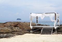 与白色树荫的简单的木材海滩棚子在岩石海滩 免版税库存照片