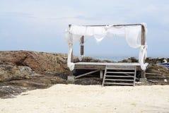 与白色树荫的简单的木材海滩棚子在岩石海滩 库存图片