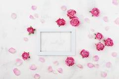 与白色框架、桃红色玫瑰花和瓣的婚礼大模型在轻的台式视图 美好的花卉模式 平的位置样式 免版税库存图片