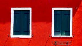 与白色框架的两个窗口在红颜色墙壁上 库存照片
