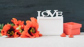 与白色框架的情人节大模型与在织品和黑背景的词爱、红色鸦片花和礼物盒 华伦泰 免版税库存照片