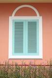 与白色框架的淡色蓝色窗口在桃红色墙壁上 免版税库存图片