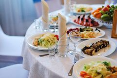 与白色桌布、玻璃饮料的和食物的欢乐桌在宴会的餐馆 免版税库存照片