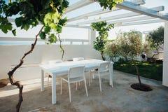 与白色桌的大阳台和椅子在有藤和橄榄树的一个白色屋顶下 免版税库存图片