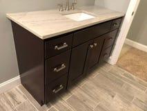 与白色水槽和镀铬物龙头在黑暗的木内阁,在卫生间里面的砖地的花岗岩工作台面 图库摄影