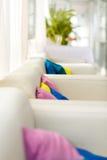 与白色沙发和五颜六色的枕头的明亮的内部 库存照片