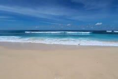 与白色沙子和波浪在Bukit地区,巴厘岛的蓝色海滩 免版税库存图片