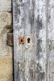 与白色油漆切削的和削皮的被风化的木门 免版税库存照片