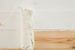 与白色油漆的漆滚筒刷子在木背景 免版税图库摄影