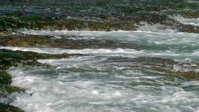 与白色泡沫流程的不尽的海浪从棕色岩石 股票录像