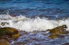 与白色波浪的海表面在海滩石头 飞溅并且滴下海水 免版税库存图片