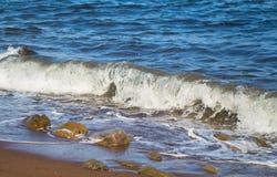 与白色波浪的海表面在海滩石头 飞溅并且滴下海水 图库摄影