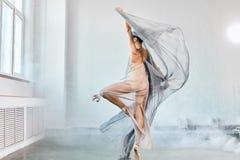 与白色流动的织品的女性跳芭蕾舞者 流程形状和运动 免版税图库摄影