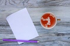 与白色淡紫色花和干净的白色方格的纸一张的芬芳维生素清凉茶与一支紫色铅笔的在木 免版税库存照片