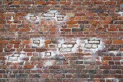 与白色片断的破旧的被风化的肮脏的红砖墙壁背景 免版税库存图片