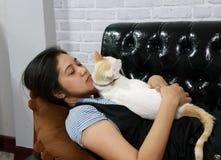 与白色猫的妇女睡眠在黑沙发 免版税库存照片