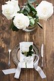 与白色玫瑰的浪漫桌设置作为装饰、葡萄酒餐具、银器和装饰在木板 库存图片