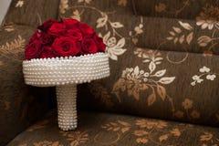 与白色珍珠和红色浪漫玫瑰的典雅的婚礼花束 免版税库存照片