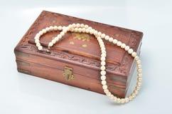 与白色珍珠项链的小木胸口 库存照片