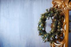 与白色的圣诞节花圈和金在黑暗的木前门背景的中看不中用的物品装饰 免版税图库摄影