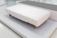 与白色盖子的全新的沙发床适合了板料和木腿 库存照片