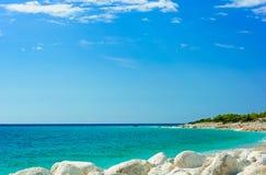 与白色石头的美丽的地中海狂放的海滩,希腊 库存照片