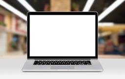 与白色空白的显示的膝上型计算机大模型在书桌上在办公室 免版税库存图片