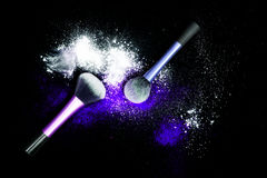 与白色粉末的构成刷子溢出了在黑背景的闪烁尘土 在新年` s党的构成刷子与明亮的颜色 库存照片