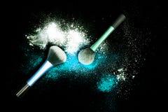 与白色粉末的构成刷子溢出了在黑背景的闪烁尘土 在新年` s党的构成刷子与明亮的颜色 图库摄影