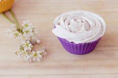 与白色结霜的香草在桌上的杯形蛋糕和花 免版税库存照片