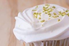 与白色结霜的香草在桌上的杯形蛋糕和花 图库摄影