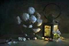 与白色翠菊花束的静物画在一个投手的水,被点燃从一个古老灯笼的生存光,大蒜片断和 图库摄影