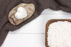 与白色腌制槽用食盐的心形的浴炸弹在木碗 免版税库存照片