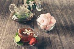 与白色苹果计算机开花的草莓茶在玻璃杯用桃红色蛋白软糖和一个美丽的玻璃水壶 有选择性 免版税库存图片