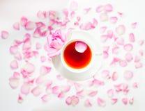 与白色茶的Flatlay、桃红色玫瑰、玫瑰花瓣和桃红色 免版税库存图片