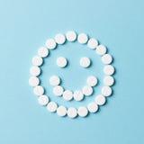 与白色药片的微笑的面孔 库存图片