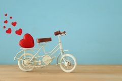 与白色葡萄酒自行车玩具的情人节浪漫背景和对此的闪烁红色心脏在木桌 库存照片