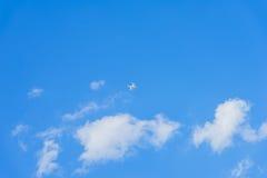 与白色蓬松云彩纹理的蓝天 在天空的上流飞行直升机,寄生虫, quadrocopter 对现代背景 免版税库存图片