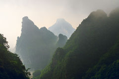 与白色薄雾史诗山风景的巨大的岩石山剪影 免版税库存照片