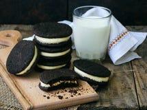 与白色蛋白软糖奶油和杯的自创巧克力曲奇饼在黑暗的背景的牛奶 免版税库存图片